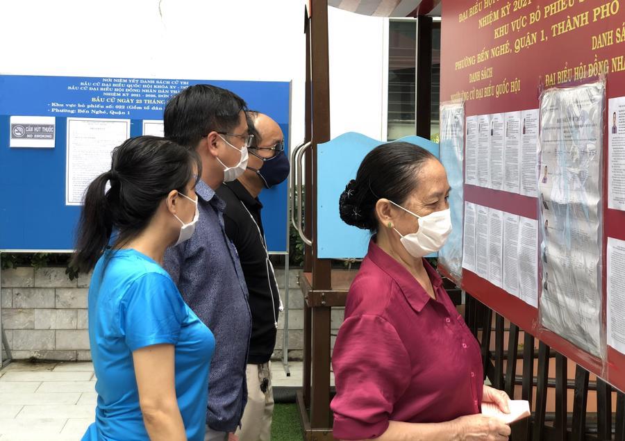 Các cử tri tổ 38, phường Bến Nghé, Quận 1 đangxem danh sách đại biểu được niêm yết để chọn lựa.