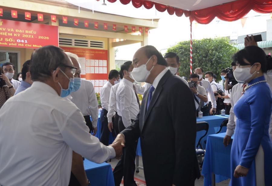 Chủ tịch nước Nguyễn Xuân Phúc bắt tay, thăm hỏi cử tri tại tổ bầu cử số 10 (khu phố 7, Thị trấn Củ Chi). Ảnh: VOV