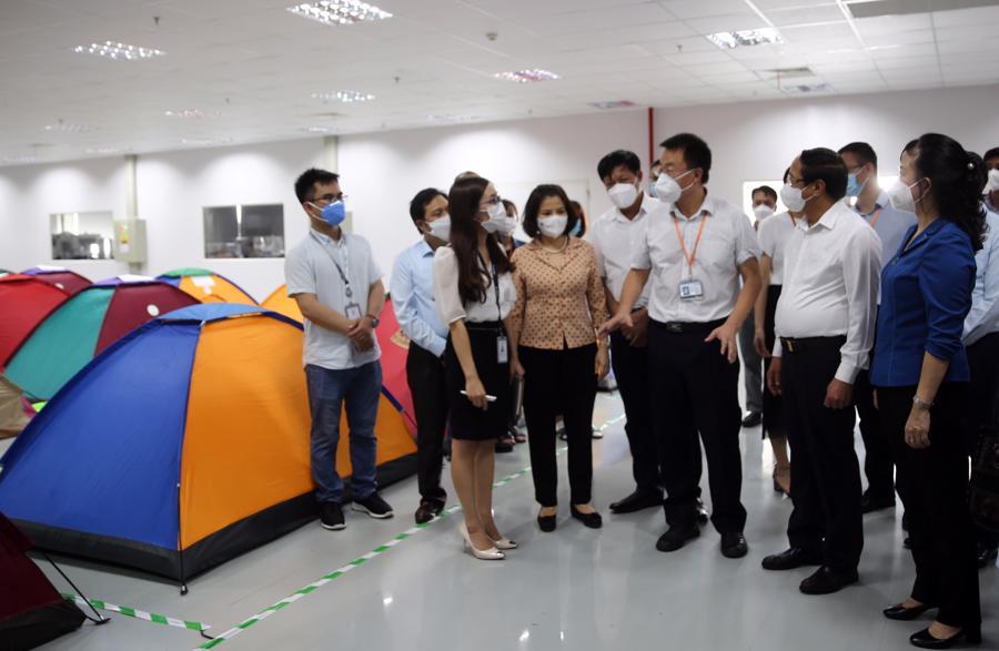 """Phó Thủ tướng Lê Văn Thành (thứ 2 bên phải) nghe lãnh đạo Công ty Goertek báo cáo về mô hình """"vừa sản xuất, vừa chống dịch"""" - Ảnh: VGP/Đức Tuân"""