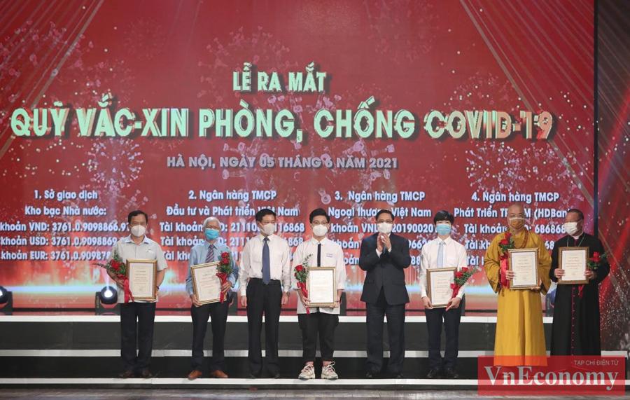 Thủ tướng Chính phủ Phạm Minh Chính cùng Bộ trưởng Bộ Tài chính Hồ Đức Phớc trao chứng nhận và hoa cảm ơn những đóng góp của đại diện các tầng lớp nhân dân vào Quỹ vaccine phòng, chống Covid-19.