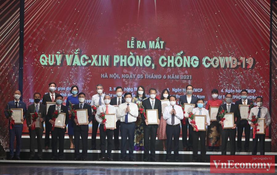 Phó Thủ tướng Lê Văn Thành cùngBộ trưởng Bộ Y tế Nguyễn Thanh Longtrao chứng nhận và hoa cảm ơn đại diện các doanh nghiệp.
