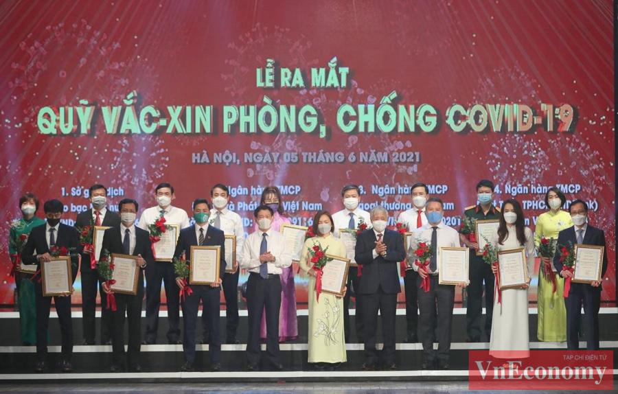 Chủ tịch Ủy ban Trung ương MTTQ Việt Nam Đỗ Văn Chiến cùngBộ trưởng Bộ Tài chính Hồ Đức Phớc trao chứng nhận và hoa cảm ơn các doanh nghiệp đóng góp cho Quỹ.