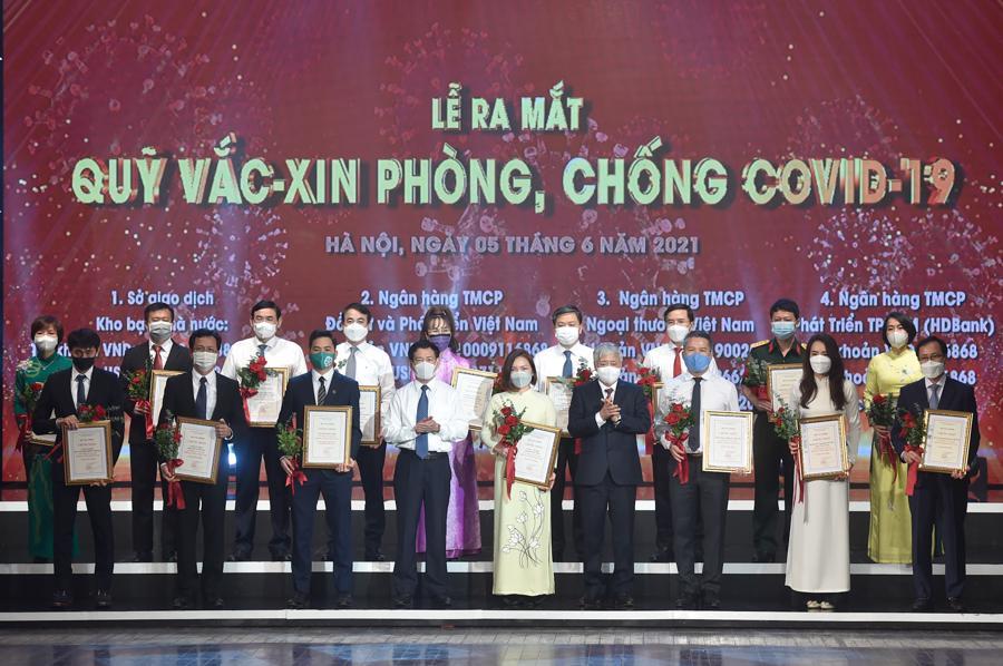 Chủ tịch Ủy ban Trung ương MTTQ Việt Nam Đỗ Văn Chiến, Bộ trưởng Bộ Tài chính Hồ Đức Phớc và đại diện bộ ngành, DN đóng góp cho Quỹ vaccine phòng chống COVID-19. Ảnh VGP.