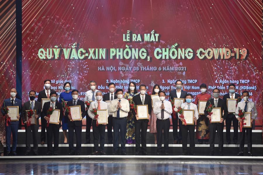 Phó Thủ tướng Lê Văn Thành,Bộ trưởng Bộ Y tế Nguyễn Thanh Long và đại diện bộ ngành, DN đóng góp cho Quỹ vaccine phòng chống COVID-19. Ảnh VGP.