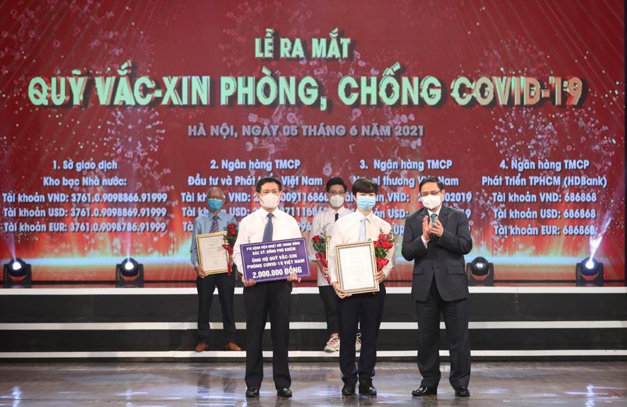Thủ tướng Chính phủ Phạm Minh Chínhtrao chứng nhận, hoa cảm ơnem Lê Đức Hiếu, học sinh Trường Phạm Hồng Thái, Ba Đình, Hà Nội, 15 tuổi. Ảnh VGP