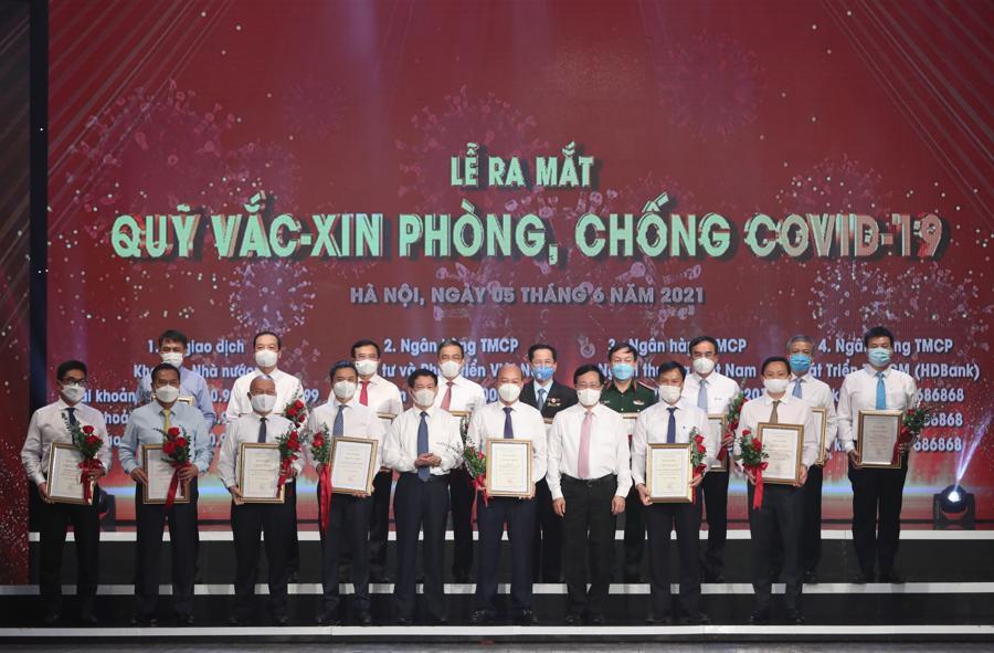 Phó Thủ tướng Phạm Bình Minh,Bộ trưởng Bộ Tài chính Hồ Đức Phớc và đại diện bộ ngành, DN đóng góp cho Quỹ vaccine phòng chống COVID-19. Ảnh: Quang Phúc.