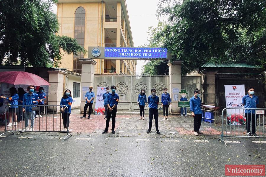 Tại điểm thi THPT Phạm Hồng Thái, lực lượng thanh niên tình nguyện tiếp sức mùa thi giúp phân luồng thí sinh từ ngoài cổng trường.