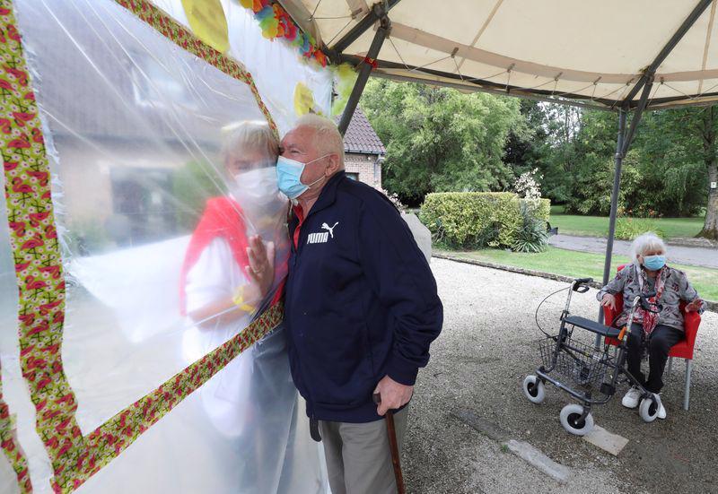 Một người cao tuổi tại một nhà dưỡng lão ở Bỉ ôm người thân qua bức tường làm bằng nhựa để tránh lây nhiễm dịch bệnh - Ảnh: Yves Herman/Reuters