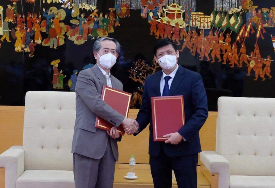 GS.TS Nguyễn Thanh Long - Bộ trưởng Bộ Y tế Việt Nam và ngài Hùng Ba - Đại sứ đặc mệnh toàn quyền nước CHND Trung Hoa - trao biên bản bàn giao lô hàng viện trợ gồm 500.000 liều vaccine và hơn 500.000 bơm kim tiêm.