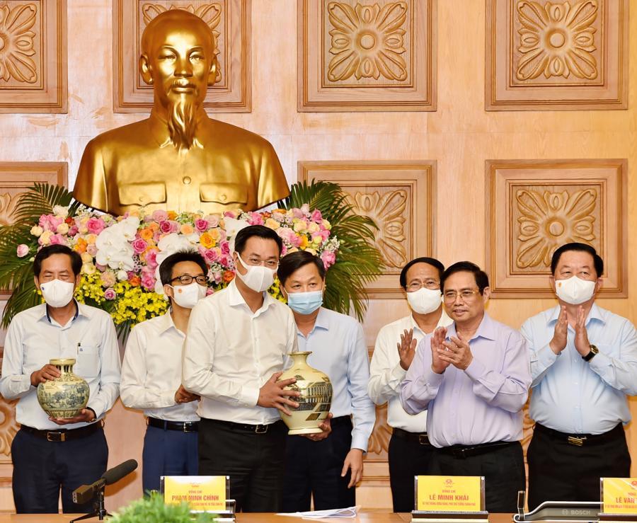 Thủ tướng Phạm Minh Chính trao quà tặng các cơ quan báo chí tại cuộc gặp mặt - Ảnh: VGP