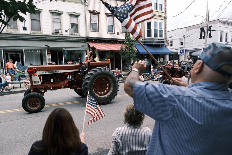 Người dân Mỹ vẫy cờ khi xem diễu hành mừng Quốc khánh ở Saugerties, New York ngày 4/7 - Ảnh: Getty/WSJ.