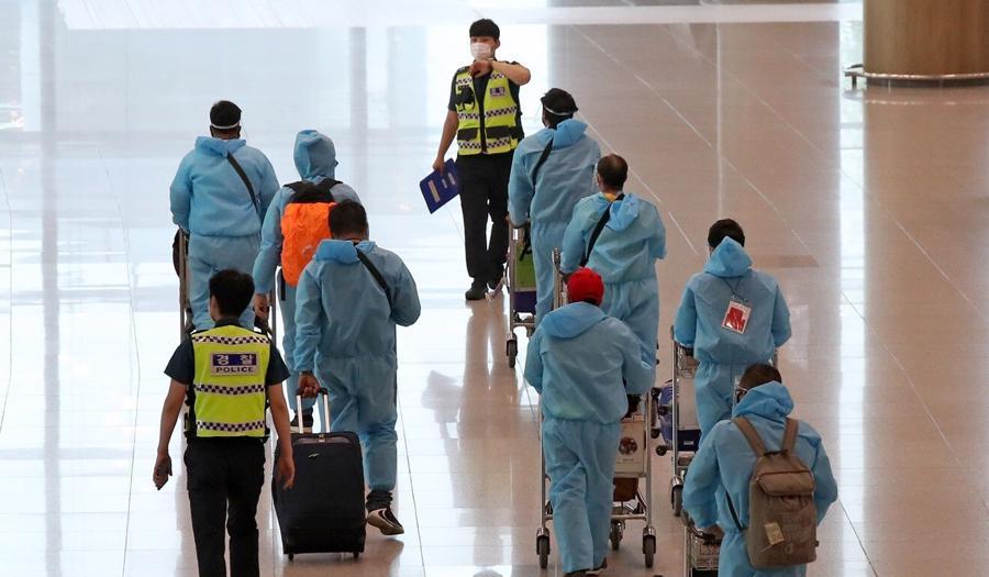 Người nhập cảnh từ Ấn Độ - một quốc gia có nguy cơ cao - được cảnh sát hướng dẫn khi đến Sân bay Quốc tế Incheon của Hàn Quốc hôm 2/7 - Ảnh: Yonhap / EPA