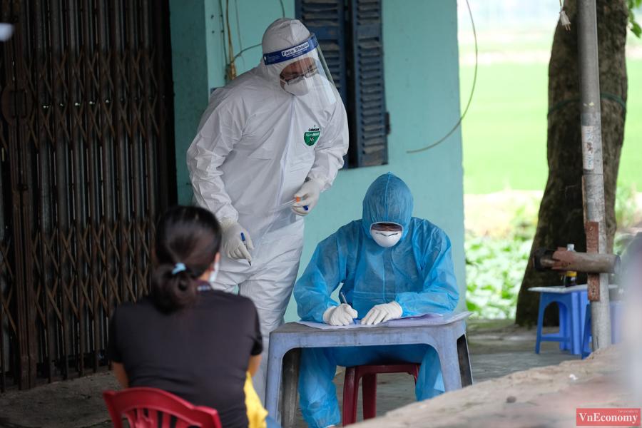 Cán bộ y tế đãtrưng dụng một cửa hàng sửa chữa xe máy ngay đầu con đường dẫn vào thôn để làm nơi lấy mẫu xét nghiệm cho người dân.