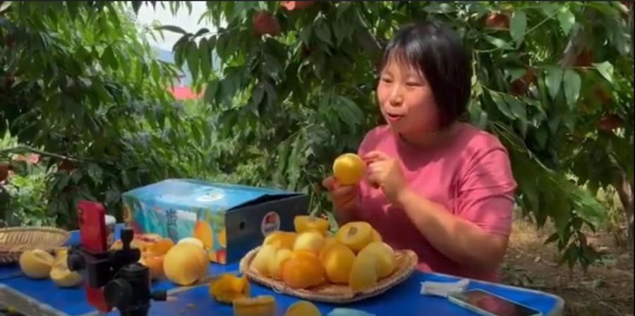 Bà Guo Chengcheng bán đào trong một buổi phát trực tiếp vào ngày 2 /7 - Ảnh: Bloomberg