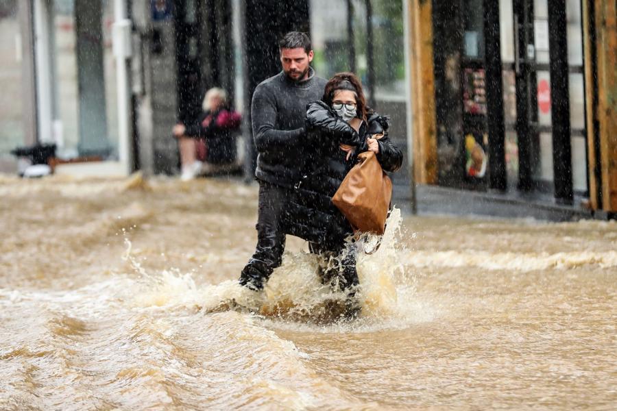Một người đàn ông giúp một phụ nữ đi qua con phố bị ngập ở Spa, Bỉ hôm 14/7 - Ảnh: AFP/Getty Images