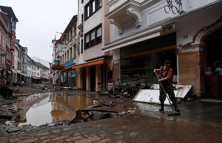 Một người dân dọn dẹp con phố bị tàn phá sau trận mưa lớn ở Bad Neuenahr-Ahrweiler, Đức - Ảnh: AFP/Getty Images