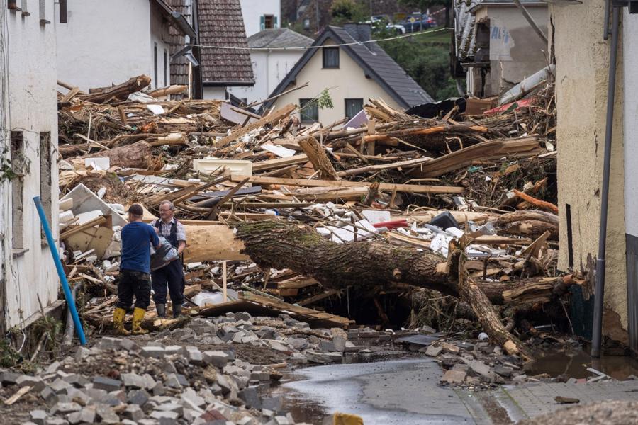 Hai người đàn ông đang chuyển các vật dụng còn sót lại từ đống đổ nát của những ngôi nhà bị sập do mưa lũ ở Schuld, miền tây nước Đức- Ảnh: AFP/Getty Images