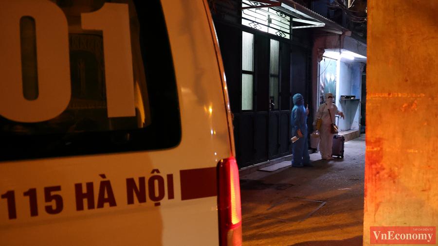 Bệnh nhân F0 mang đồ đạc ra khỏi nhà, chuẩn bị lên xe cứu thương.