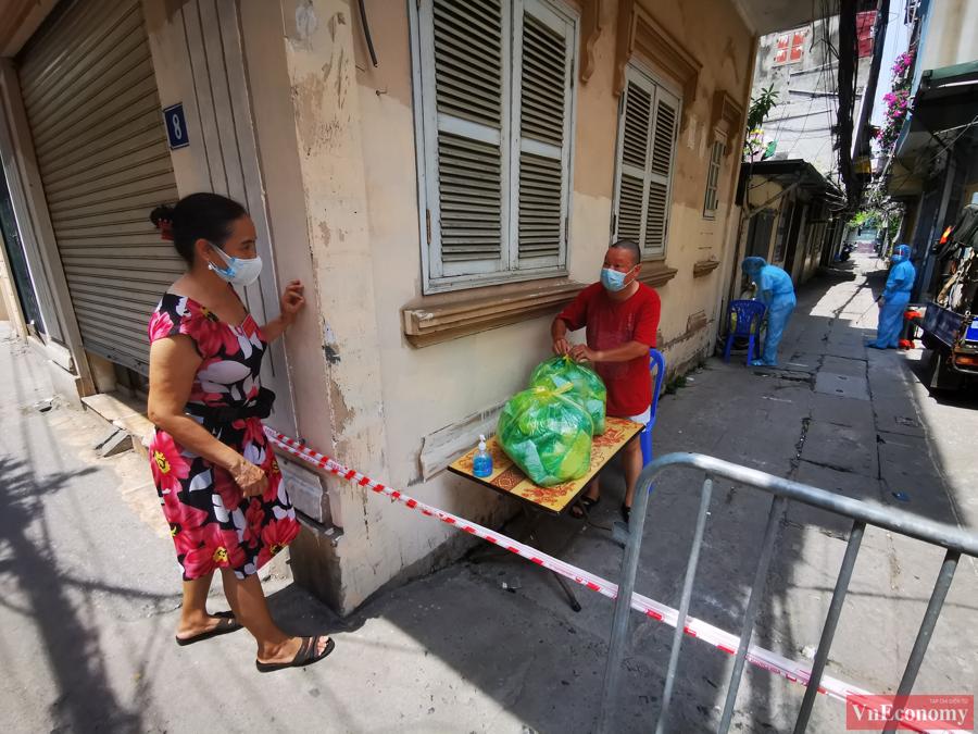Tại khu vực hàng rào cách ly có đặt một chiếc bàn để nhận đồ tiếp tế của người dân bên ngoài gửi vào bên trong và ngược lại.