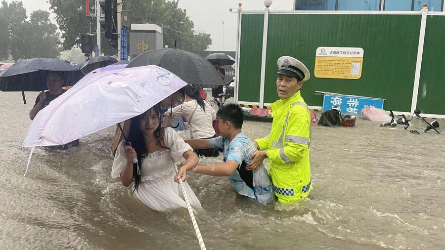 Cảnh sát hướng dẫn người dân đi qua một đoạn đường ngập trong cơn mưa lớn tại Trịnh Châu ngày 20/7 - Ảnh: AP