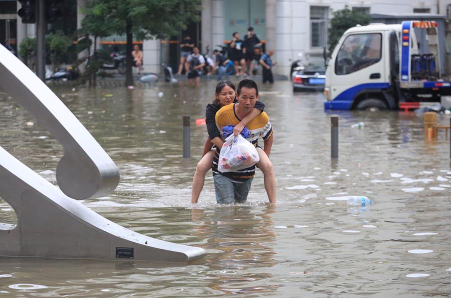Một người đàn ông cõng một phụ nữ lội qua con đường ngập lụt sau trận mưa lớn ở Trịnh Châu ngày 21/7 - Ảnh: China Daily/Reuters