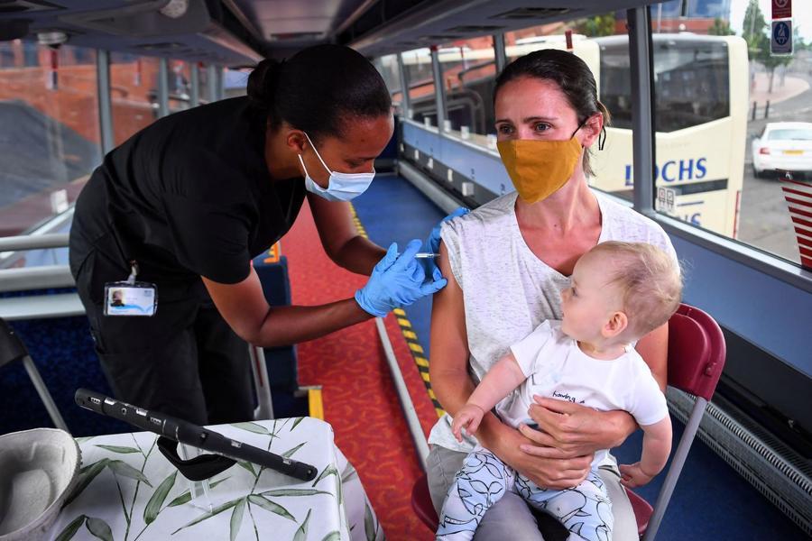 Một phụ nữ đi tiêm vaccine Covid-19 ở Glasgow, Anh - Ảnh: Getty/WSJ.