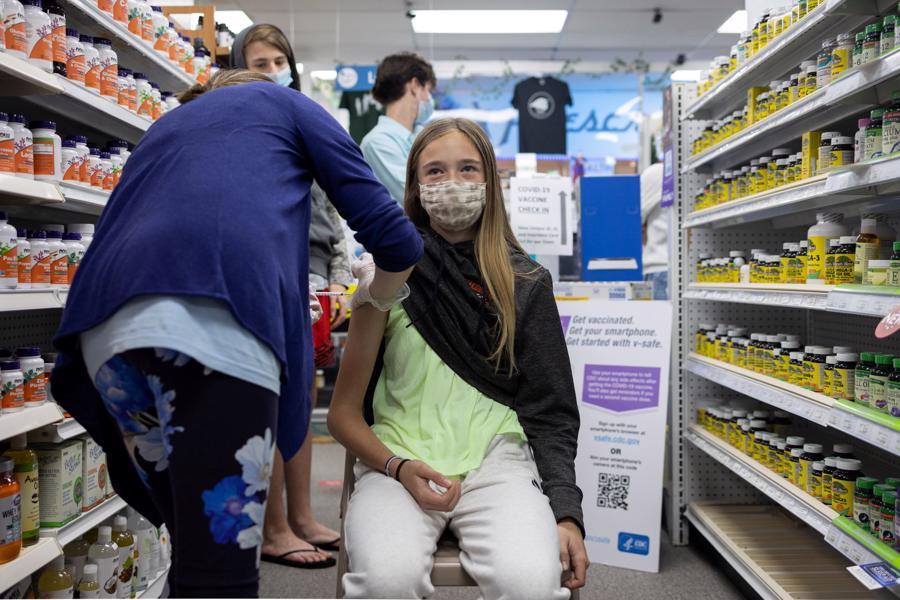 Một bé gái 13 tuổi được tiêm phòng Covid-19 bằng vaccine Pfizer tại một hiệu thuốc ở Pennsylvania, Mỹ, tháng 5/2021 - Ảnh: Reuters.