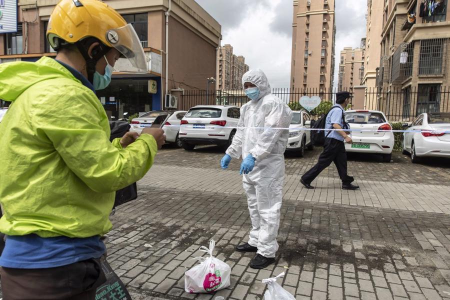 Một nhân viên giao hàng đưa hàng thiết yếu đến một khu cư dân bị phong toả ở Thượng Hải, Trung Quốc hôm 3/8 - Ảnh: Bloomberg.