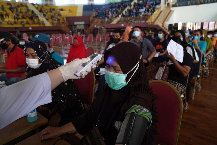 Kiểm tra nhiệt độ cơ thể tại một cơ sở tiêm chủng ngừa Covid ở Jakarta, Indonesia, hôm 4/8 - Ảnh: Bloomberg.