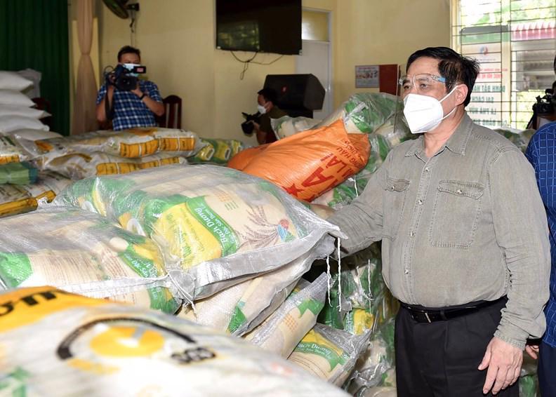 Thủ tướng tới nhà văn hóa xã Thạnh Phú, huyện Vĩnh Cửu, nơi tập kết các nguồn vận động, tài trợ để cung ứng lương thực, thực phẩm cho các đối tượng khó khăn trên địa bàn (Ảnh VGP).