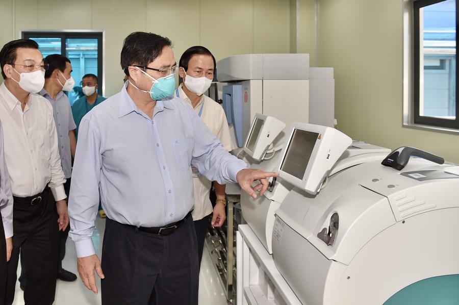 Thủ tướng Phạm Minh Chính kiểm tra hệ thống máy xét nghiệm Covid-19 tại phòng Lab của bệnh viện.
