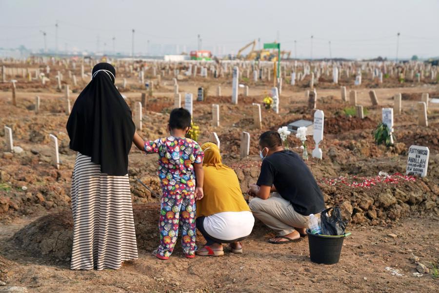 Người thân thăm mộ một người tử vong vì Covid-19 ở Jakarta, Indonesia, hôm 18/8/2021 - Ảnh: Bloomberg.