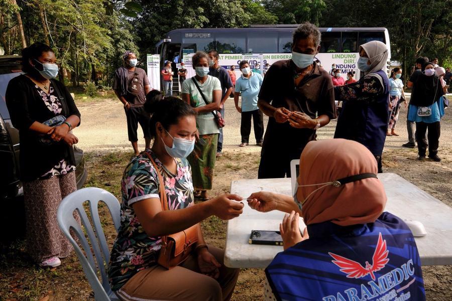 Người dân đi tiêm vaccine Covid tại một điểm tiêm chủng lưu động ở Selangor, Malaysia, đầu tháng 7/2021 - Ảnh: Bloomberg.