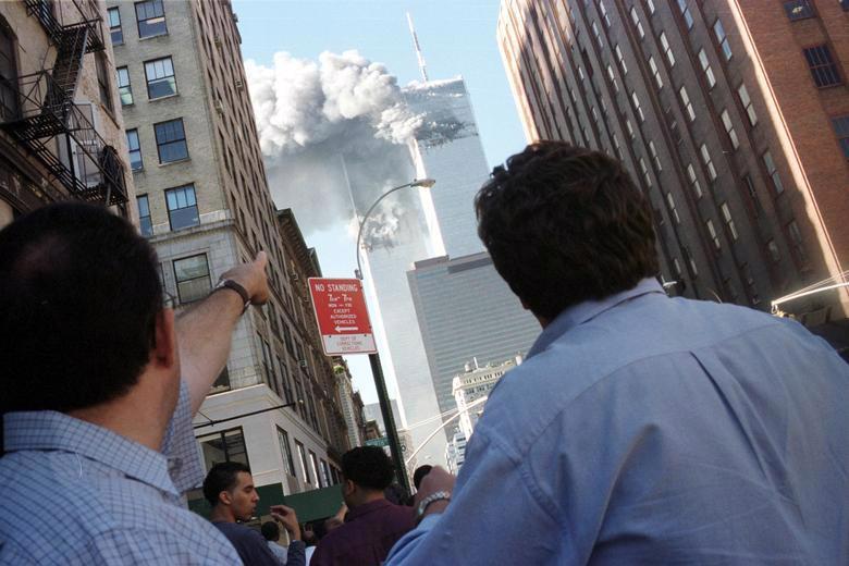 Người đi đường chứng kiến vụ tấn công vào hai tòa tháp của Trung tâm Thương mại Thế giới (WTC) - Ảnh: Reuters