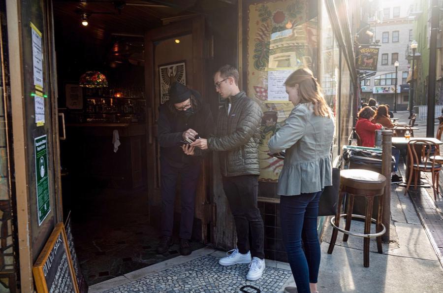 Kiểm tra tình trạng tiêm chủng tại cửa một quán bar ở San Francisco, Mỹ hôm 24/8 - Ảnh: Bloomberg.