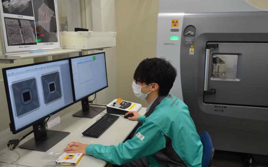 Một kỹ sư tại Oki Engineering đang kiểm tra tính xác thực của con chip - Ảnh: Nikkei Asia