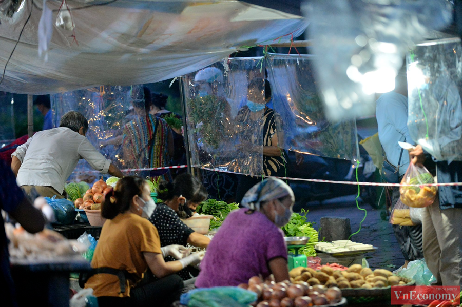 Tại chợ Ngã Tư Sở (phường Ngã Tư Sở, quận Đống Đa), bà con tiểu thương chủ động căng dân, căng tấm chắn giọt bắn đểphòng chống dịch bệnh.