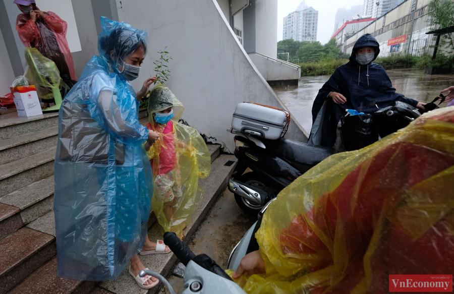 Người thân đội mưa đến đón các công dân phường Thanh Xuân Trung về nơi cư trú.Hiện nhà riêng của họ bên trong ngõ 328 và ngõ 330 đường Nguyễn Trãi vẫn trong diện phong tỏa, nên sau khi rời nơi cách ly, người dân này phải tự tìm kiếm nơi ở tạm.