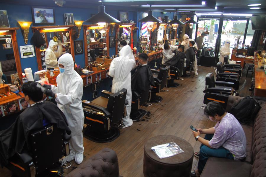 Để đảm bảo an toàn, nhiều nhân viên và thợ cắt tóc được trang bị đồ bảo hộ chống dịch trong ngày mở cửa trở lại. Ảnh: Dạ Thảo (báo Thanh Niên)
